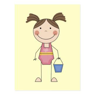 Menina da praia com camiseta e presentes do balde cartão postal