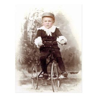Menino no triciclo cartão postal