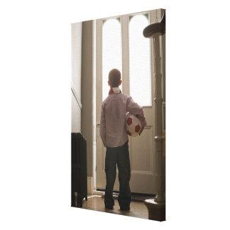 Menino no vestíbulo com bola de futebol