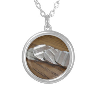 Moedas metálicas vazias na mesa de madeira colar banhado a prata