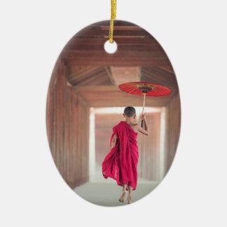 Monge budista com guarda-chuva vermelho ornamento de cerâmica oval