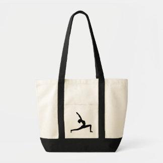 Mulher da silhueta da ioga que levanta sacolas do bolsa tote