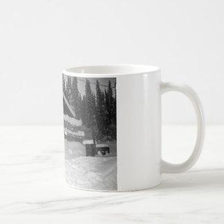 neve da cabine do inverno que goteja fora da caneca de café