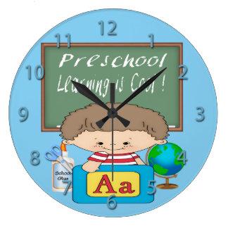O menino pré-escolar que aprende é pulso de relógio de parede