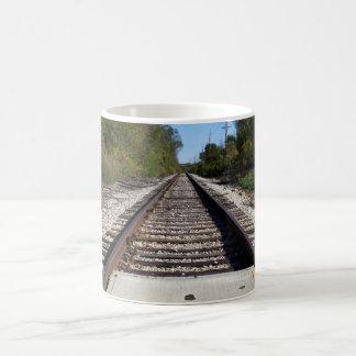 O trem de estrada de ferro segue a foto caneca