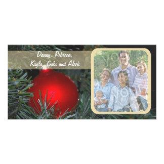 Ornamento de vidro vermelho em um cartão com fotos cartão com foto