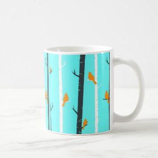 Os pássaros empoleiram o branco caneca de café
