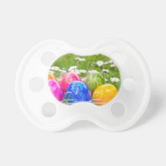 Ovos da páscoa pintados coloridos na grama com chupeta