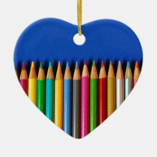 Pastéis coloridos do lápis no fundo azul ornamento de cerâmica coração