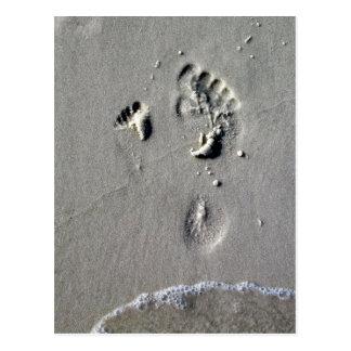Pegadas do pai & da criança na areia cartões postais