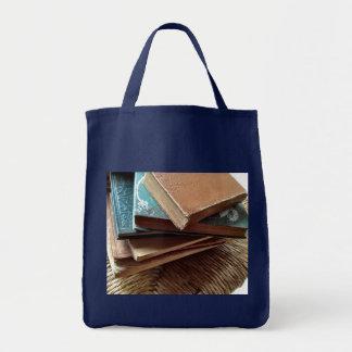 pilha de livros na sacola velha do mantimento da bolsa tote