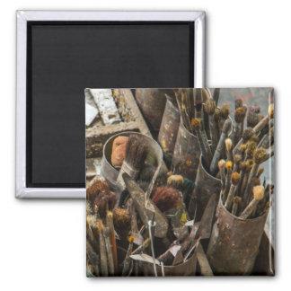 Pincéis e pintura do artista no caso de madeira ímã quadrado