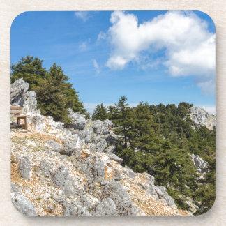 Porta-copo Bench na montanha rochosa com árvores e o céu azul