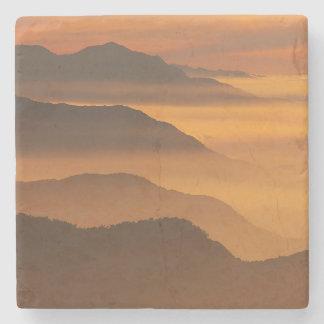 Porta-copo De Pedra A montanha alaranjada da névoa do por do sol