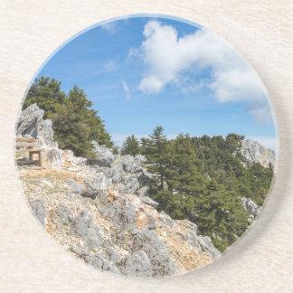 Porta-copos Bench na montanha rochosa com árvores e o céu azul