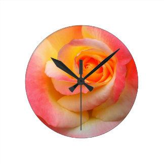 Produtos alaranjados, amarelos, e do rosa do rosa  relógios de paredes