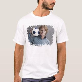 Redhead que guardara uma bola de futebol em seu camisetas