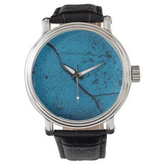 Relógio rachado azul do fundo da parede