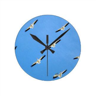 Relógio Redondo Guindastes que voam no céu azul