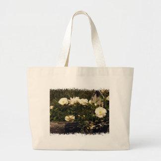 Rosas brancos em um saco da cerca bolsa de lona
