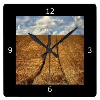 Sido e campo de trigo ido com trilhas do trator relógios de paredes