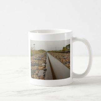 Trilhas de estrada de ferro em um dia chuvoso caneca de café