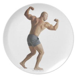 um bodybuilder masculino caucasiano adulto mostra  pratos