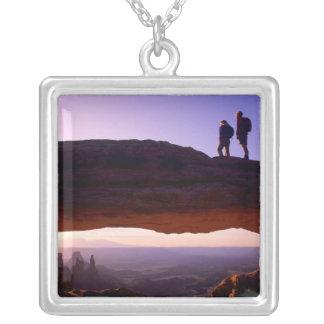 Um casal olha o nascer do sol sobre do arco do colar banhado a prata