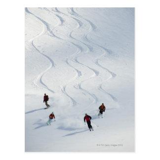 Um grupo de esquiadores backcountry segue seu guia cartão postal