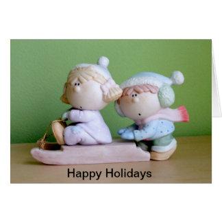 Um par adorável de miúdos em um trenó cartão comemorativo