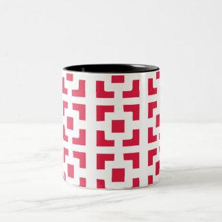 Uma caneca vermelha do café do teste padrão do