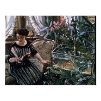 Uma mulher que lê perto de um tanque do peixe cartão postal
