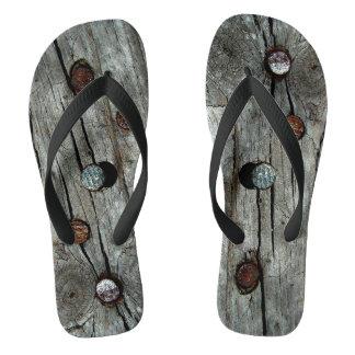 Unhas na fotografia de madeira em chinelos
