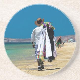 Vendedor na praia porta copos de arenito